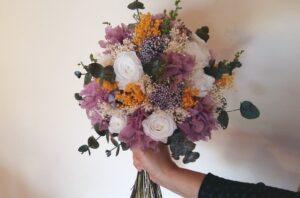 """Aquest és el ram de núvia de la Yolanda. Quan em va contactar, la Yolanda ja tenia molt clar el que volia per al seu casament: un ram de flors preservades a joc amb el seu tocat del cabell. Volia que fos un ram rodonet i amb tons malva i violeta, amb roses blanques i tocs de groc per donar un aire més primaveral. Vam escollir les flors juntes i li vaig anar enviant fotos del procés. Tot i que les fotos li anaven, quan el va veure en persona es va adonar de que """"en directe"""" era encara molt més bonic."""